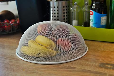 Fruit stored under a mesh dome to deter fruit flies